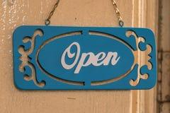 Um sinal que pendura na porta da rua aberta Imagens de Stock Royalty Free