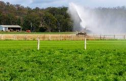 Um sistema de extinção de incêndios em colheitas molhando de um campo fotografia de stock