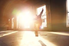 Um skater novo em um chapéu branco e em uma camiseta preta faz um truque com um patim salta em uma construção abandonada no Foto de Stock