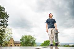 Um skater novo está com um skate no fundo da paisagem da cidade fotos de stock royalty free