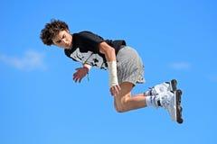 Um skater profissional na patinagem Inline salta a competição Imagem de Stock Royalty Free