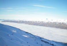 Um skifield acima de um vale completamente das nuvens Fotografia de Stock Royalty Free