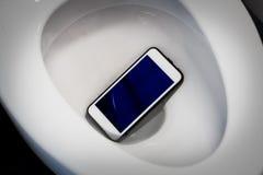 Um smartphone branco deixou cair em uma bacia de toalete Fotos de Stock Royalty Free