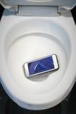 Um smartphone branco deixou cair em uma bacia de toalete Imagens de Stock Royalty Free