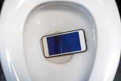 Um smartphone branco deixou cair em uma bacia de toalete Fotografia de Stock