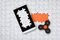 Um smartphone grande moderno com um tela táctil e um girador encontram-se em um enigma de serra de vaivém branco em um estado mon foto de stock