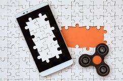 Um smartphone grande moderno com um tela táctil e um girador encontram-se em um enigma de serra de vaivém branco em um estado mon fotografia de stock