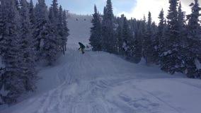 Um snowboarder em um terno e em um capacete brilhantes, passando entre os abeto cobertos de neve nos trampolins pequenos e filme
