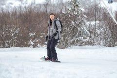 Um snowboarder fêmea redigido está esquiando com seu snowboard Fotos de Stock Royalty Free