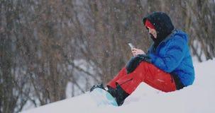 Um snowboarder masculino que senta-se na neve toma fotos no telefone de uma paisagem bonita do recurso para redes sociais filme