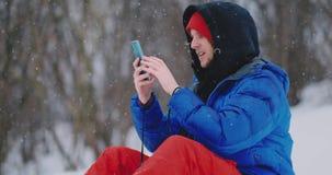 Um snowboarder masculino que senta-se na neve toma fotos no telefone de uma paisagem bonita do recurso para redes sociais video estoque