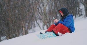 Um snowboarder masculino que senta-se na neve toma fotos no telefone de uma paisagem bonita do recurso para redes sociais vídeos de arquivo