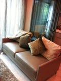 Um sofá de couro do falso em uma sala de visitas por uma cozinha fotos de stock royalty free