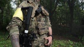 Um soldado armado com um rifle e um uniforme militar que estão nas madeiras e fuma Um grupo de homens armados na camuflagem vídeos de arquivo