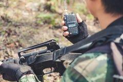 Um soldado armado que realiza e que usa a radiocomunicação no campo de batalha Foto de Stock Royalty Free