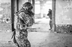 Um soldado na engrenagem do combate visa o inimigo imagens de stock