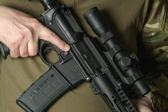 Um soldado que guarda um rifle com uma vista telescópica imagem de stock