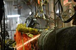 Um soldador está moendo a junção da solda no encanamento a pouca distância do mar foto de stock