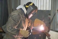 Um soldador solda os encanamentos tecnologicos com soldadura de arco manual para uma refinaria de petróleo em Rússia Jun??o solda foto de stock royalty free
