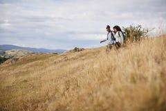 Um sorriso adulto novo dos pares da raça misturada ao andar através de um campo para baixo durante uma caminhada da montanha fotos de stock