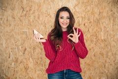 Um sorriso brilhante, menina doce com gestos longos ondulados do cabelo diz que o alimento em sua mão é delicioso Linguagem gestu Foto de Stock