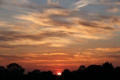 Um Sun quase ajustado em céus nebulosos foto de stock royalty free