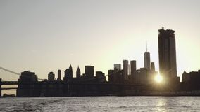 Um sunflare do por do sol brilha através da skyline do Lower Manhattan e da ponte de Brooklyn em New York, Estados Unidos filmada video estoque