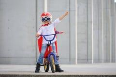 Um super-herói engraçado, pequeno Imaginação do menino do conceito Childchood feliz foto de stock