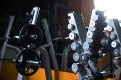 Um suporte com barbells em um gym Suporte dos pesos em um fundo borrado Equipamento de esportes Aptidão, exercício, treinando fotografia de stock