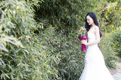 Um suporte da foto/retrato do casamento da jovem mulher por bambus imagens de stock royalty free