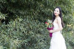 Um suporte da foto/retrato do casamento da jovem mulher por bambus foto de stock royalty free
