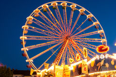 Um suporte da roda de Ferris iluminado contra o céu da noite Fotografia de Stock Royalty Free