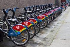 Um suporte de bicicletas do aluguer com o logotipo dos patrocinadores em Dublin City Cent imagens de stock royalty free