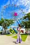 Um suporte de sorriso da menina na frente dos ferris coloridos roda no parque de Santorini imagem de stock royalty free