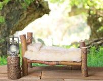 Um suporte digital do estúdio recém-nascido da cama feito dos ramos de árvore do bordo japonês com um fundo da natureza do prado  imagens de stock royalty free
