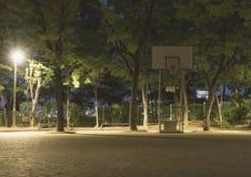 Um suporte do basquetebol e uma configuração da luz do revérbero em um campo de jogos exterior na noite foto de stock