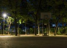 Um suporte do basquetebol e uma configuração da luz do revérbero em um campo de jogos exterior na noite fotos de stock
