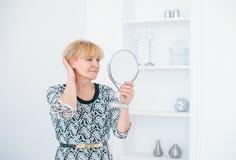 Um suporte superior bonito da mulher em uma sala branca e olhar no espelho pequeno imagem de stock