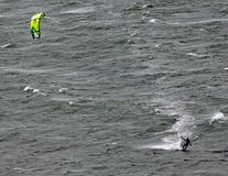 Um surfista do papagaio move-se através da baía de Lyall em Wellington New Zealand em um dia tormentoso cinzento fotografia de stock