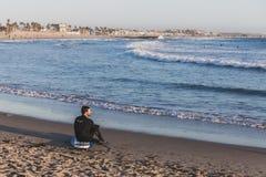 Um surfista que senta-se na praia em Venice Beach foto de stock