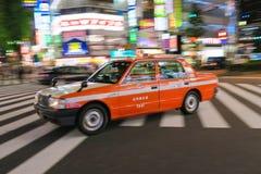 Um táxi passa através do cruzamento de Shinjuku no Tóquio, Japão Fotos de Stock Royalty Free