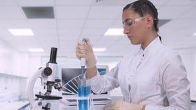 Um técnico de laboratório fêmea transfere uma amostra fluida azul aos tubos diferentes usando um micropipette ao sentar-se em uma video estoque
