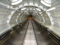 Um túnel com uma escada rolante, Imagem de Stock