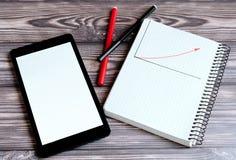 Um tablet pc preto com uma tela leve, para seu texto, está encontrando-se em uma tabela de madeira ao lado de um bloco de notas fotografia de stock