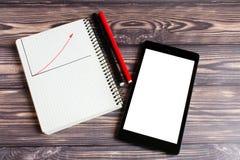 Um tablet pc preto com uma tela leve, para seu texto, está encontrando-se em uma tabela de madeira ao lado de um bloco de notas imagem de stock royalty free