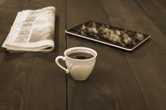 Um tampão do jornal do café e da tabuleta - cor do sepia fotos de stock royalty free