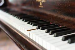 Um teclado de piano de cauda antigo, com anos de desgaste, e um colaram a chave foto de stock royalty free