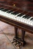 Um teclado de piano de cauda do vintage, com anos de desgaste, e um colaram a chave foto de stock royalty free