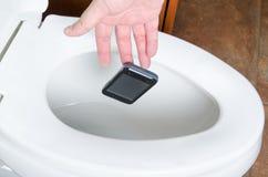 Um telefone celular deixado cair no Toliet Fotos de Stock Royalty Free