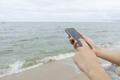 Um telefone celular texting do homem na praia fotografia de stock royalty free